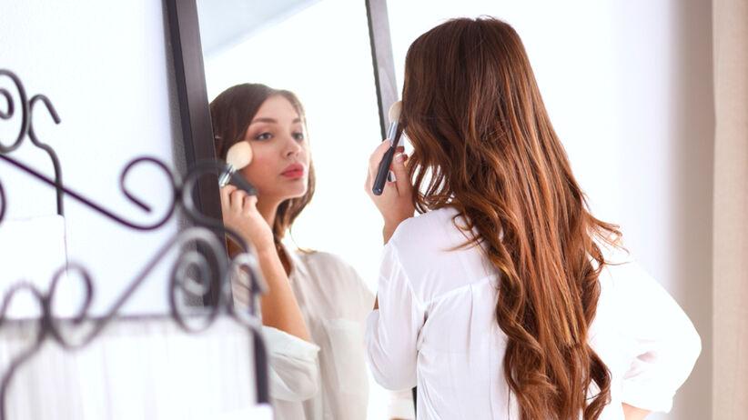 Kobieta maluje się, przeglądając się w lusterku