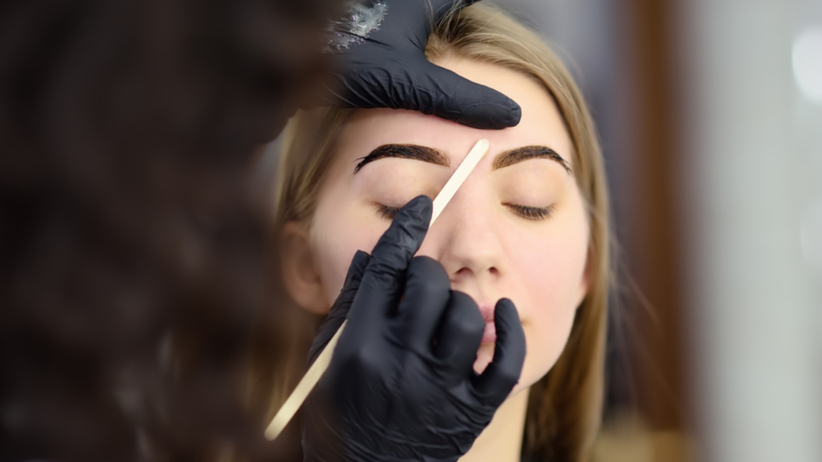 Kobieta robi u kosmetyczki makijaż permanentny brwi
