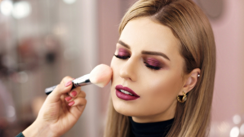 Kobieta z mocno pomalowanymi oczami siedzi u kosmetyczki i próbuje uzyskać efekt mokrej skóry