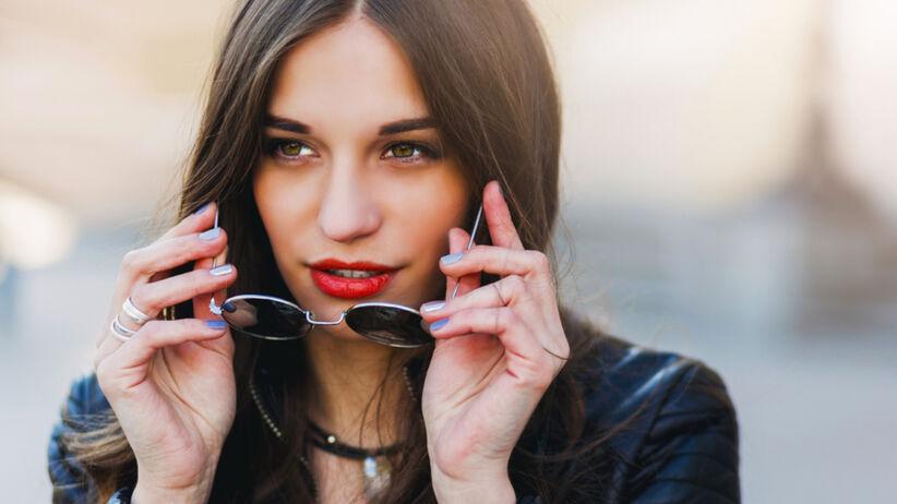 Młoda, delikatnie pomalowana dziewczyna z czerwonymi ustami i w skórzanej kurtce