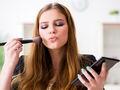 Kobieta maluje się różnymi kosmetykami