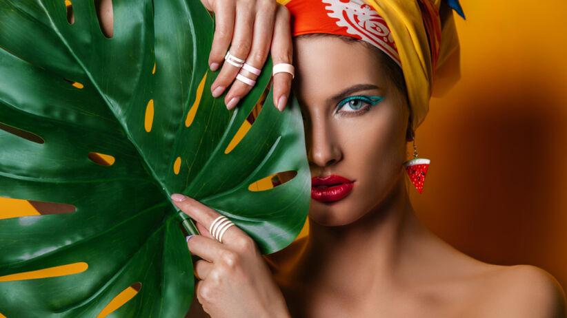 Piękna dziewczyna w żółtym turbanie i z mocnym, kolorowym makijażem oczu, chowa się za zielonym liściem