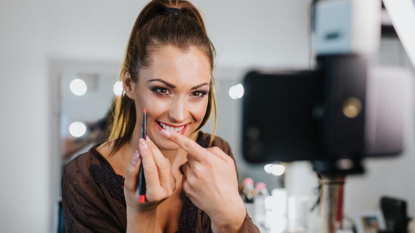 Uśmiechnięta kobieta maluje się szminką przed kamerą