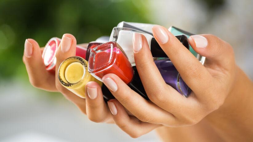 Kobieta trzyma w dłoniach różnokolorowe lakiery do paznokci