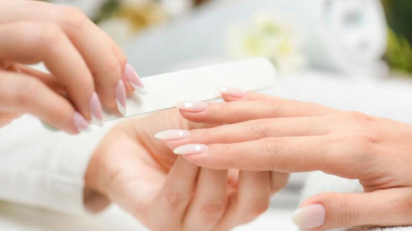Kobieta u kosmetyczki robi sobie przezroczyste paznokcie