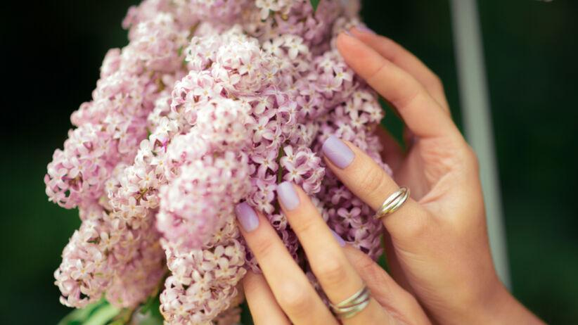 Kobieta prezentuje swoje fiołkowe paznokcie na tle fiołków