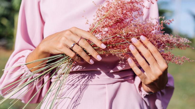 Kobieta w różowej sukience i z delikatnymi pastelowymi paznokciami trzyma kwiatki w rękach wiosną