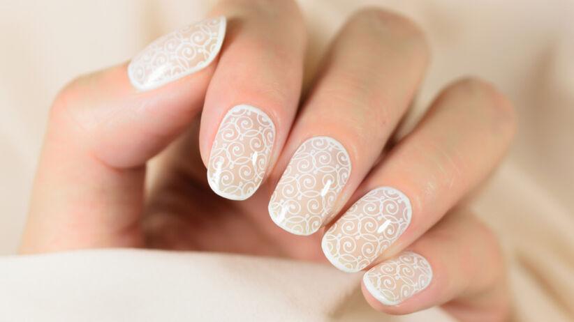 Białe kontury i wzorek na jasnych paznokciach