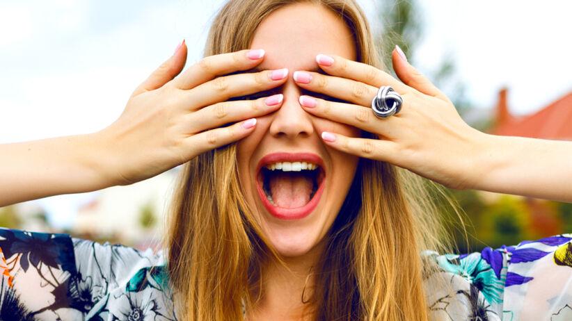 Radosna kobieta z czerwonymi ustami pokazuje pomalowane paznokcie