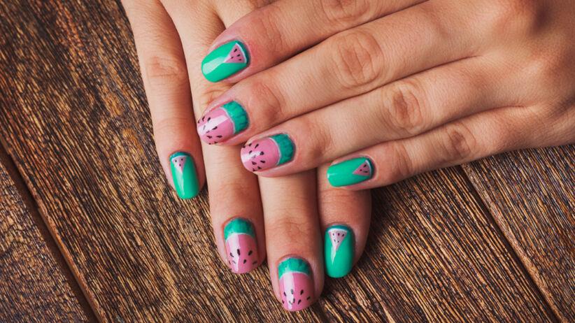 Pastelowe fruity nails z printem arbuzowym na damskich dłoniach, które są położone na drewnianym stole