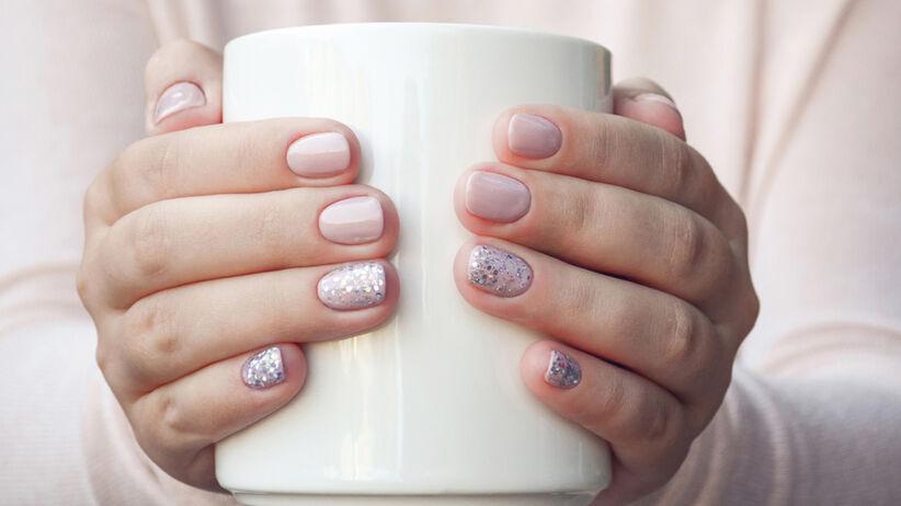 Kobieta z pięknie pomalowanymi, pastelowymi paznokciami w stylu speckled nails