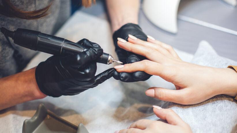 Manicurzystka robi paznokcie w salonie swojej klientce - frezuje paznokcie frezarką