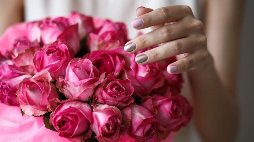 Młoda dziewczyna z modnymi paznokciami na wiosnę w kolorach pastelowych i z elementami złota trzyma w rękach bukiet róż