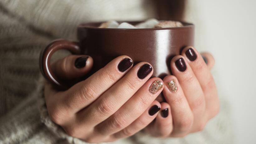 Kobieta z najmodniejszymi paznokciami na zimę 2020/2021 trzyma duży kubek z gorącym napojem
