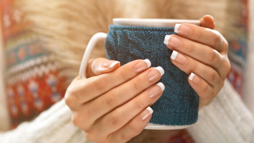 French manicure pokazany na ocieplanym kubku zimą