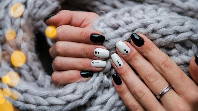 Czarno-białe paznokcie z kropkami na tle szarego szalika