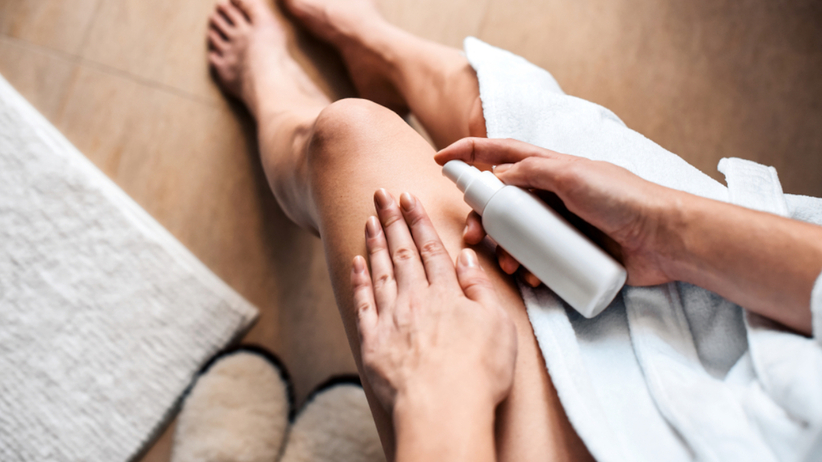 Kobieta nakłada balsam na cellulit na nogach