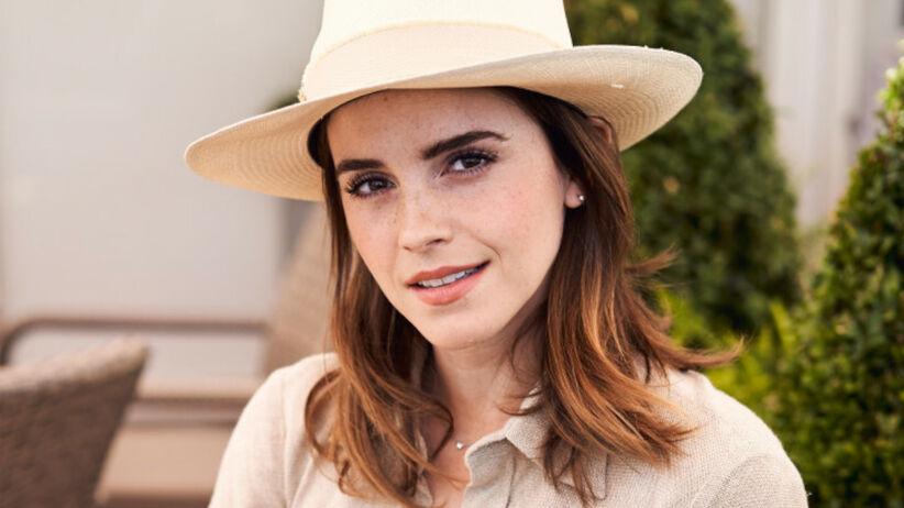 Emma Watson w naturalnej sukience i słomianym kapeluszu siedzi na fotelu