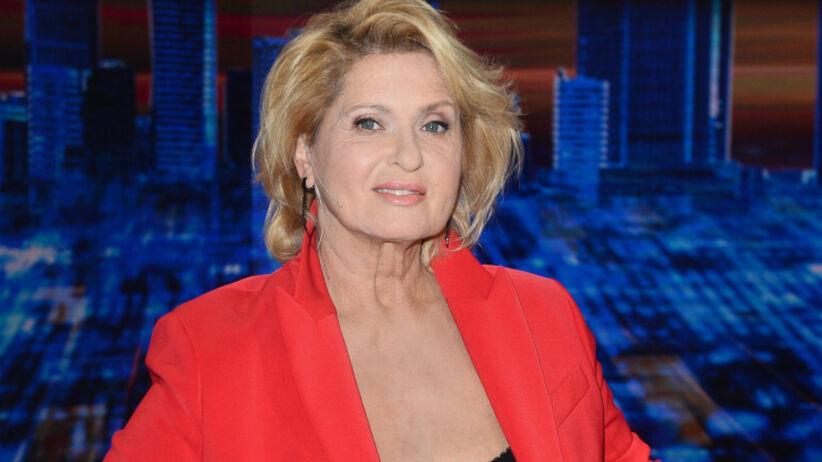 Ewa Kasprzyk w makijażu i czerwonym garniturze