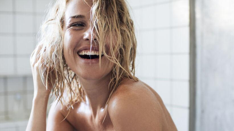 Piękna, uśmiechnięta dziewczyna w ręczniku stoi w łazience po zabiegu pielęgnacyjnym