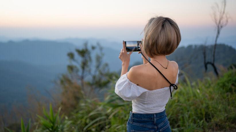 Starsza kobieta z piękną sylwetką stoi tyłem do aparatu i robi zdjęcie widoku
