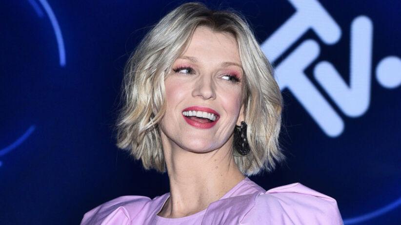 Magda Mołek w fioletowej sukience uśmiecha się do fotoreporterów