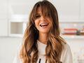 Uśmiechnięta Anna Lewandowska w białej bluzce siedzi na blacie kuchennym