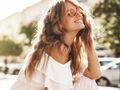 Uśmiechnięta kobieta z długimi, naturalnymi włosami i w okularach przeciwsłonecznych