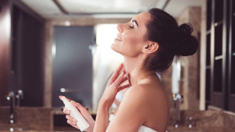 Kobieta z naszyjnikiem Wenus nakłada kosmetyk na szyję
