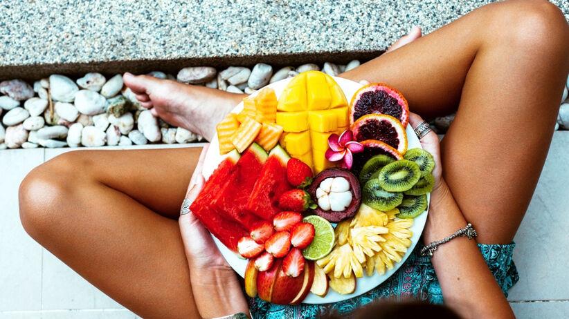 Młoda kobieta z ładną skórą trzyma talerz pełen owoców