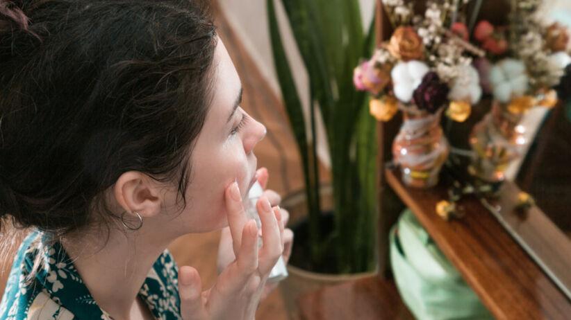 Młoda dziewczyna w kwiecistym szlafroku nakłada krem pod oczy