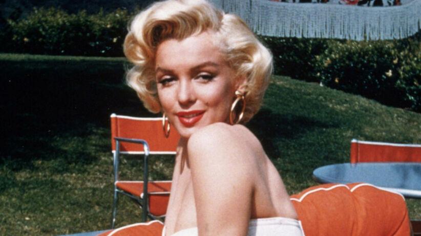 Marilyn Monroe w białym topie i spódniczce na pomarańczowym fotelu