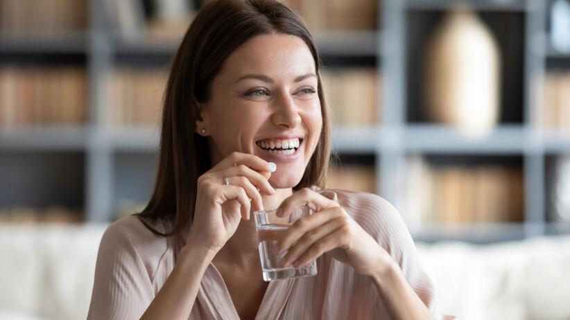 Piękna kobieta popija suplementy na wygląd wodą
