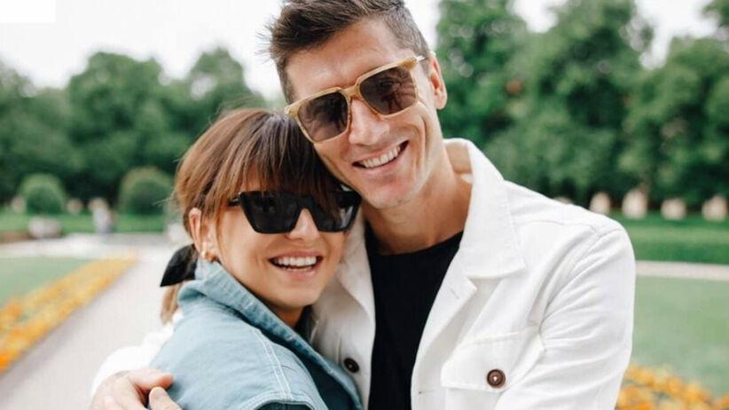 Anna Lewandowska w niebieskiej jeansowej kurtce i okularach przeciwsłonecznych i Robert Lewandowski w białej jeansowej kurtce i okularach przeciwsłonecznych przytulają się