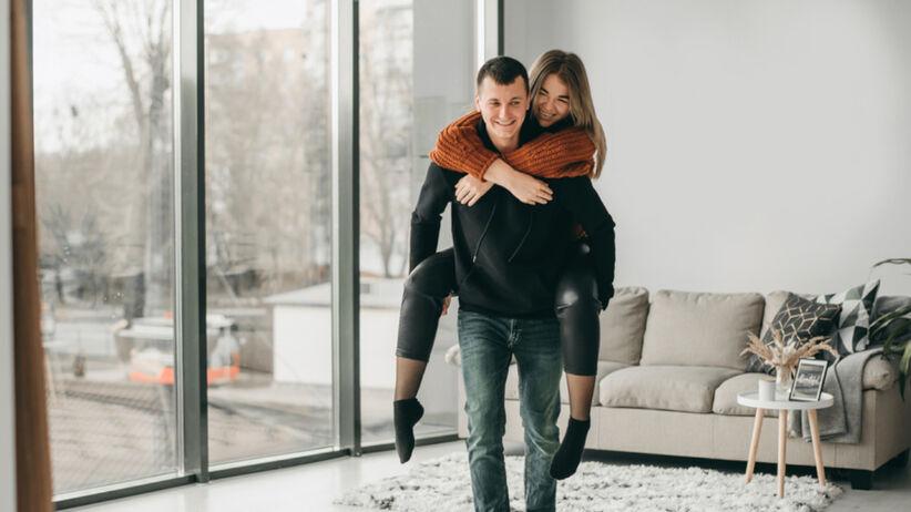 Radosna para - facet niesie na plecach swoją ukochaną po mieszkaniu
