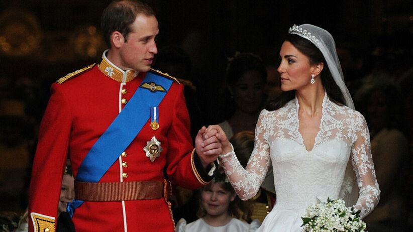 Książę William w mundurze i księżna Kate w sukni ślubnej wychodzą z kościoła po swoim ślubie