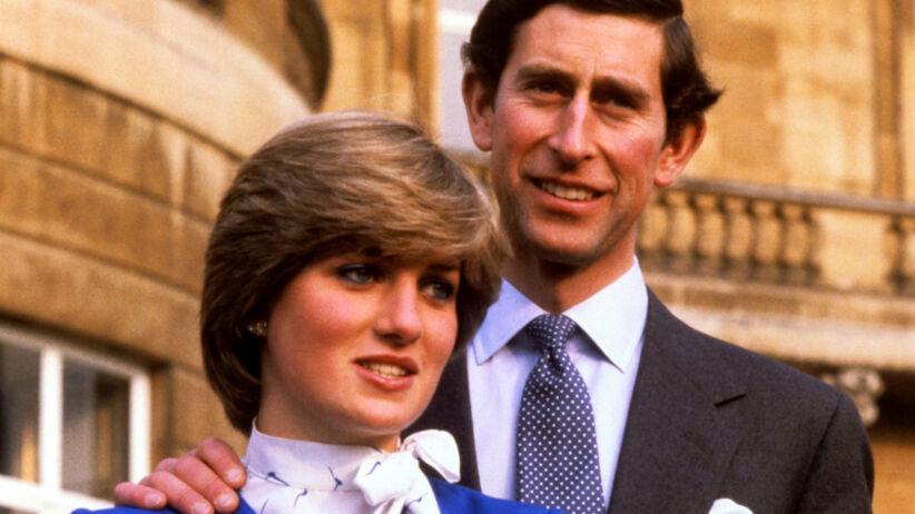 Diana Spencer w niebieskim komplecie i książę Karol w garniturze ogłaszają swoje zaręczyny