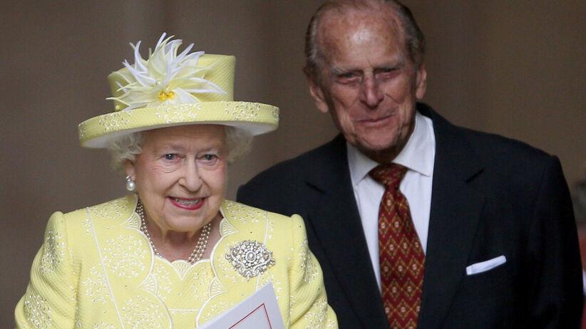 Królowa Elżbieta w żółtym stroju i książę Filip w garniturze uśmiechają się do poddanych