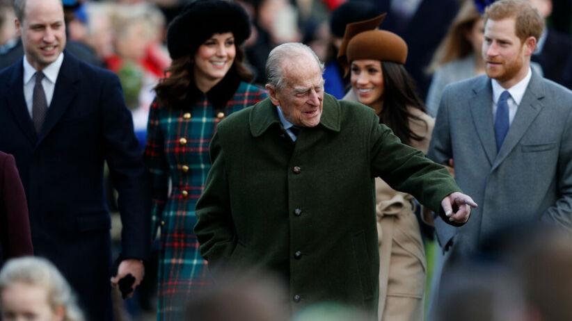 Książę Filip w zielonym płaszczu idzie przed swoimi wnukami z żonami