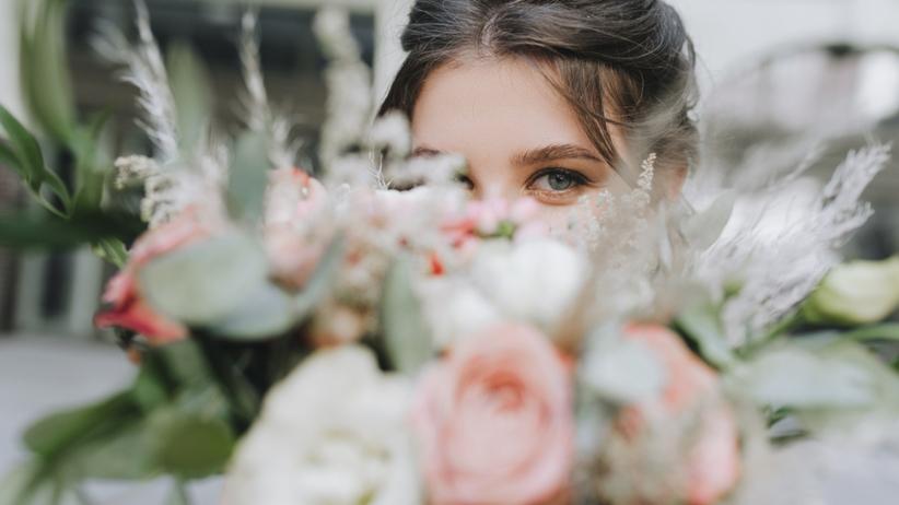 Kobieta pomalowana przed ślubem chowa się za bukietem kwiatów