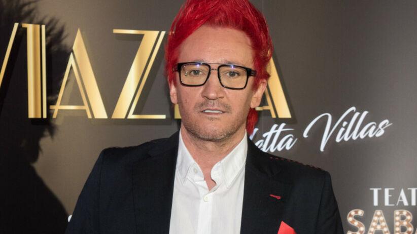 Michał Wiśniewski w garniturze i okularach optycznych z wysoko postawionymi do góry czerwonymi włosami