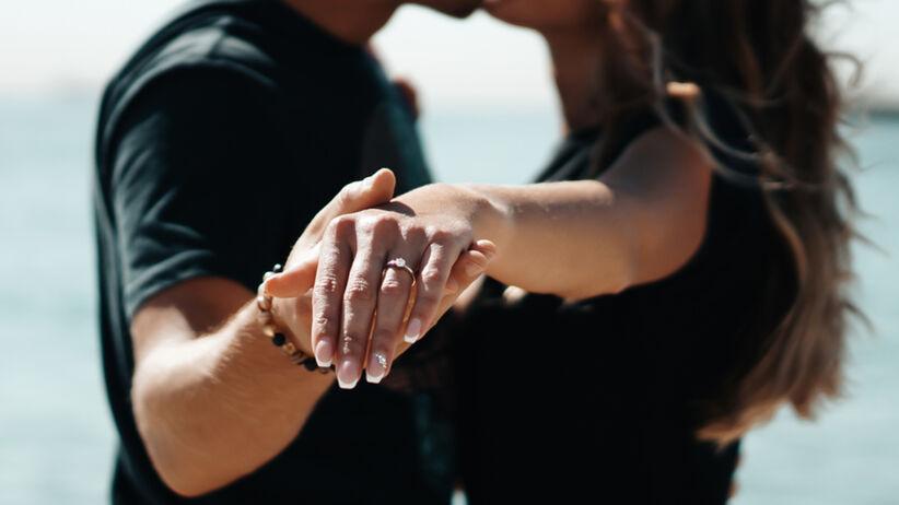 Para całuje się i prezentuje pierścionek zaręczynowy na dłoni