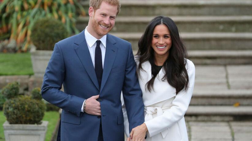 Książę Harry w granatowym garniturze i Meghan Markle w białym płaszczu z pierścionkiem zaręczynowym