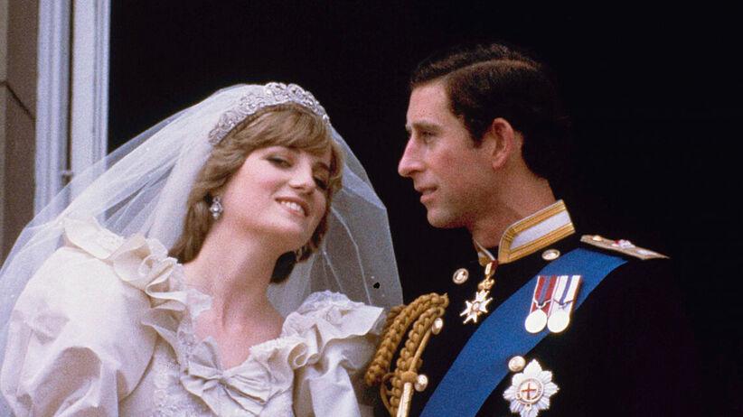 Księżna Diana w sukni ślubnej i książę Karol w mundurze stoją na balkonie i uśmiechają się do poddanych