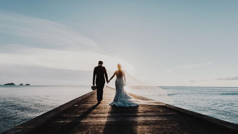 Para młoda w strojach ślubnych trzyma się za ręce i idzie po pomoście w kierunku zachodzącego nad morzem słońca
