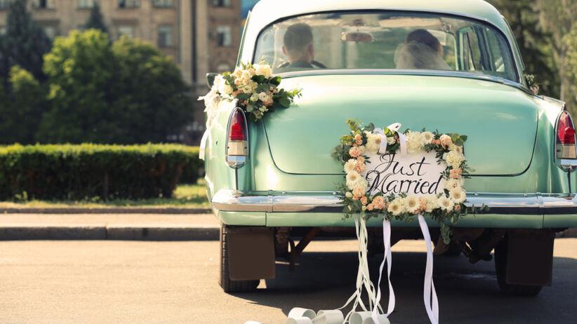 Para młoda jedzie ozdobionym samochodem na swoje wesele