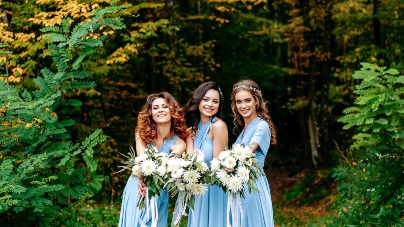 Trzy druhny w niebieskich sukienkach stoją obok lasu