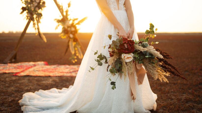 Kobieta w sukni ślubnej stoi na plaży