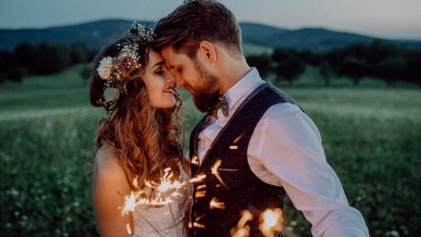 Rustykalna para młoda całuje się na swoim weselu