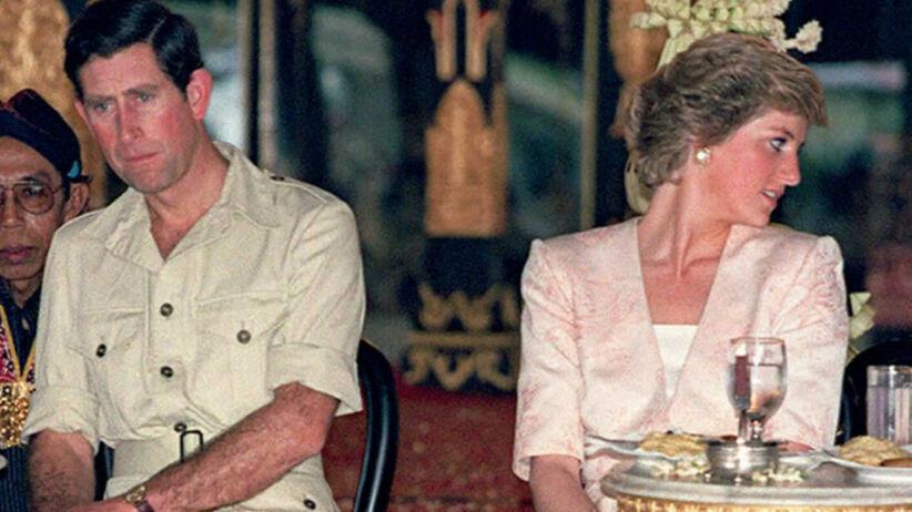 Książę Karol zdenerwowany w jasnym mundurze oraz księżna Diana smutna w różowym komplecie podczas podróży do Indii